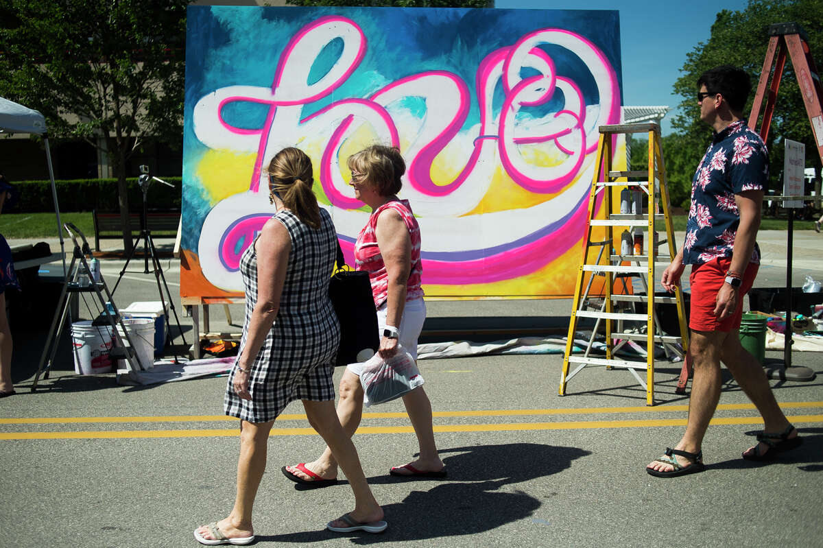 People walk past a work-in-progress mural by MarkedARTS during the Summer Art Fair Saturday, June 5, 2021 in downtown Midland. (Katy Kildee/kkildee@mdn.net)