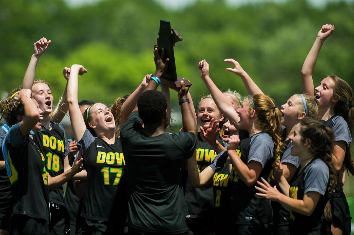 Dow players celebrate with head coach Spencer Sandow after their district championship win over Traverse City West Saturday, June 5, 2021 at H. H. Dow High School. (Katy Kildee/kkildee@mdn.net)