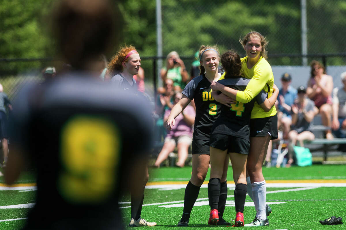 Dow's Jessica Erickson, right, hugs Libby Avery, center, after the Chargers' district championship win over Traverse City West Saturday, June 5, 2021 at H. H. Dow High School. (Katy Kildee/kkildee@mdn.net)