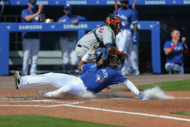 Toronto Blue Jays' Vladimir Guerrero Jr., bottom, slides across home plate to score on a single by Lourdes Gurriel Jr. during the fourth inning of the team's baseball game against the Toronto Blue Jays in Buffalo, N.Y., Saturday, June 5, 2021. (AP Photo/Joshua Bessex) Photo: Joshua Bessex, Associated Press / Copyright 2021 The Associated Press. All rights reserved