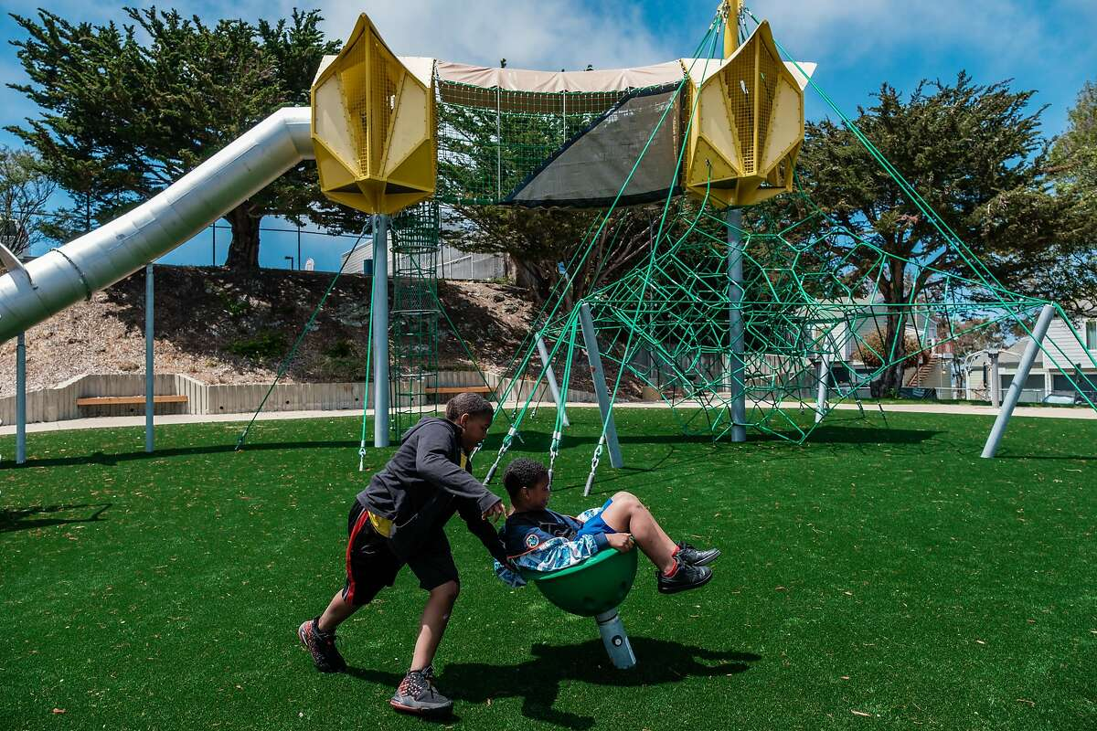 Jaquan Phillips (left), 8, and Antonio Reed, 8, test out the new spinning buckets on the renovated playground at Shoreview Park in San Francisco.