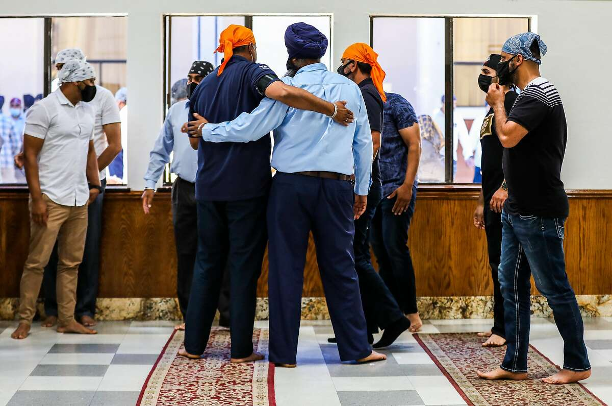 Valley Transportation Authority colleagues embrace during a memorial service for Taptejdeep Singh at the Fremont Gurdwara on Saturday. Once the shooting began at the VTA light-rail yard, Singh ran through the building warning others of the shooter before he was shot to death.