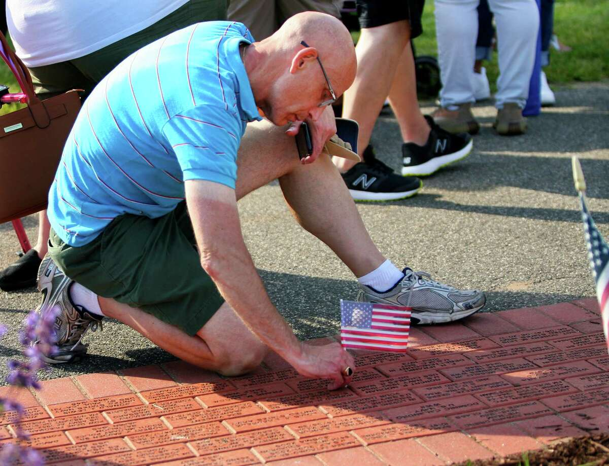 Barry Lee Cohen places a small flag on the spot of a brick dedicated to his father Irwin Cohen after the dedication ceremony for the 13th phase of the brick Veterans Walk of Honor at Bradley Point Park in West Haven, Conn., on Saturday June 5, 2021.
