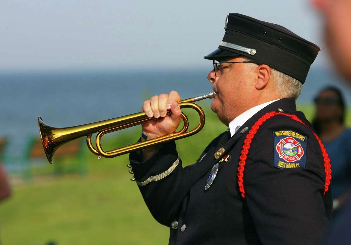 Retired West Haven firefighter Kevin McKeon plays taps during the dedication ceremony for the 13th phase of the brick Veterans Walk of Honor at Bradley Point Park in West Haven, Conn., on Saturday, June 5, 2021.