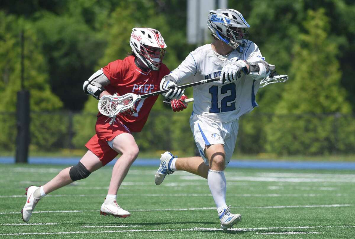 Darien's Jamison Moore (12) carries the ball on offense while Fairfield Prep's James McGrath (7) pursues during the Class L boys quarterfinals on Saturday.