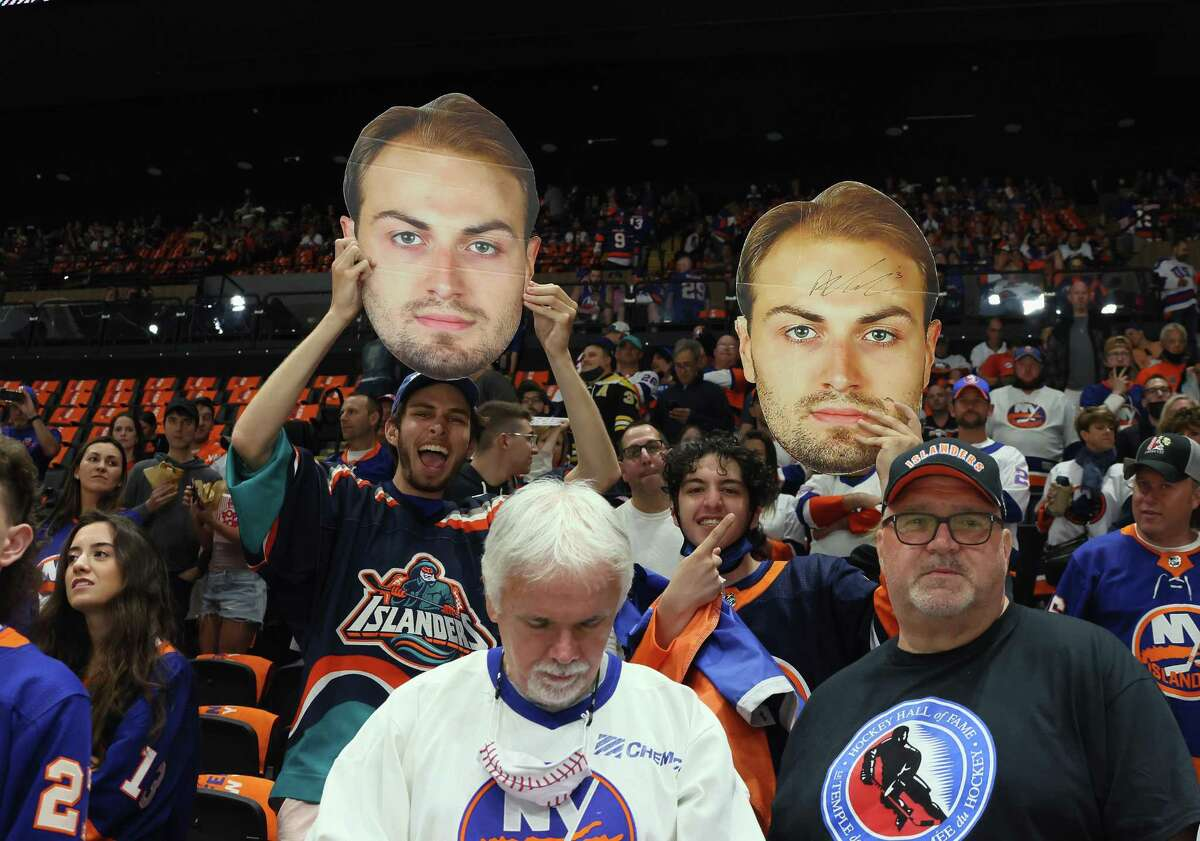 UNIONDALE, NEW YORK - JUNE 05: Fans hold up signs for Adam Pelech #3 of the New York Islanders during warm-ups prior to the game against the Boston Bruins in Game Four of the Second Round of the 2021 NHL Stanley Cup Playoffs at the Nassau Coliseum on June 05, 2021 in Uniondale, New York. (Photo by Bruce Bennett/Getty Images)