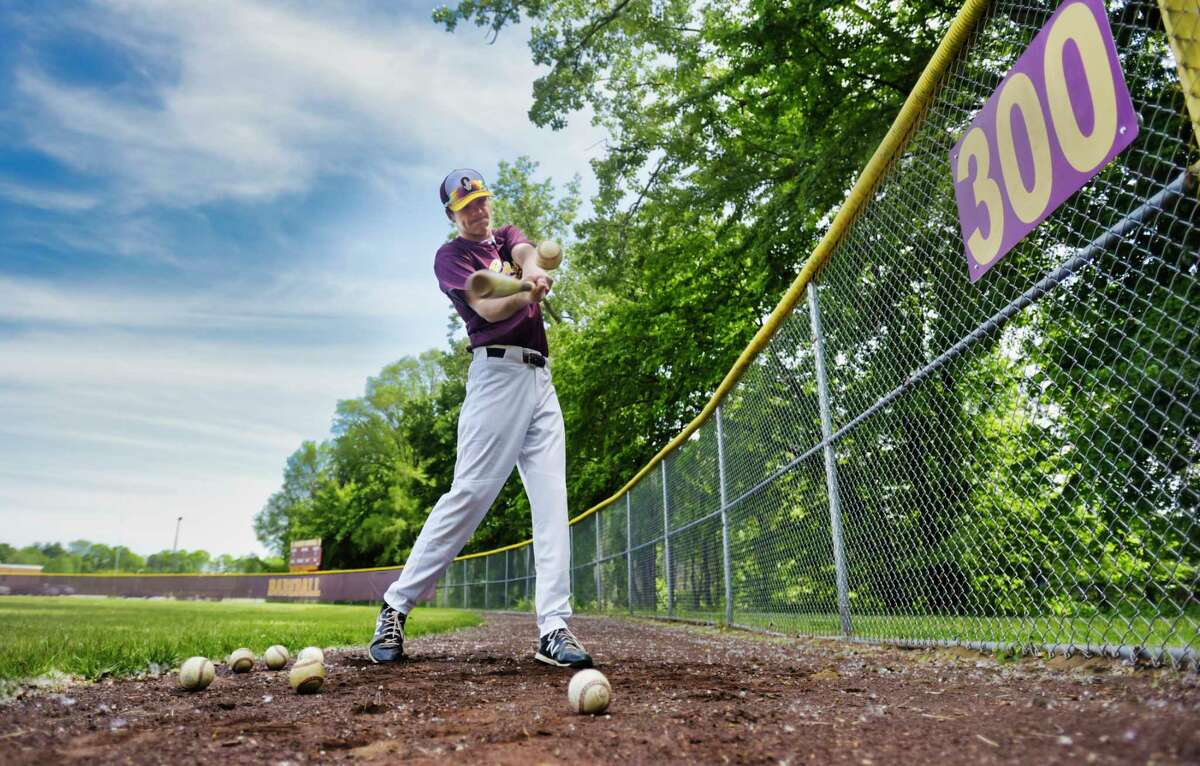 Colonie outfielder Zach Ashline, posing for a photo near the outfield fence at Colonie High School, returned from brain surgery in December to resume his baseball career.