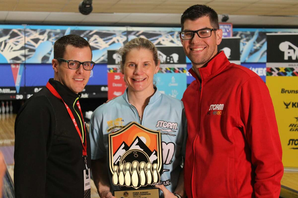 Kelly Kulick, middle, holds the 2021 PWBA Albany Open trophy with representatives of Storm, her bowling ball company,Matt McNiel, left, and Steve Jacobs. (Kurtis Von Krueger)