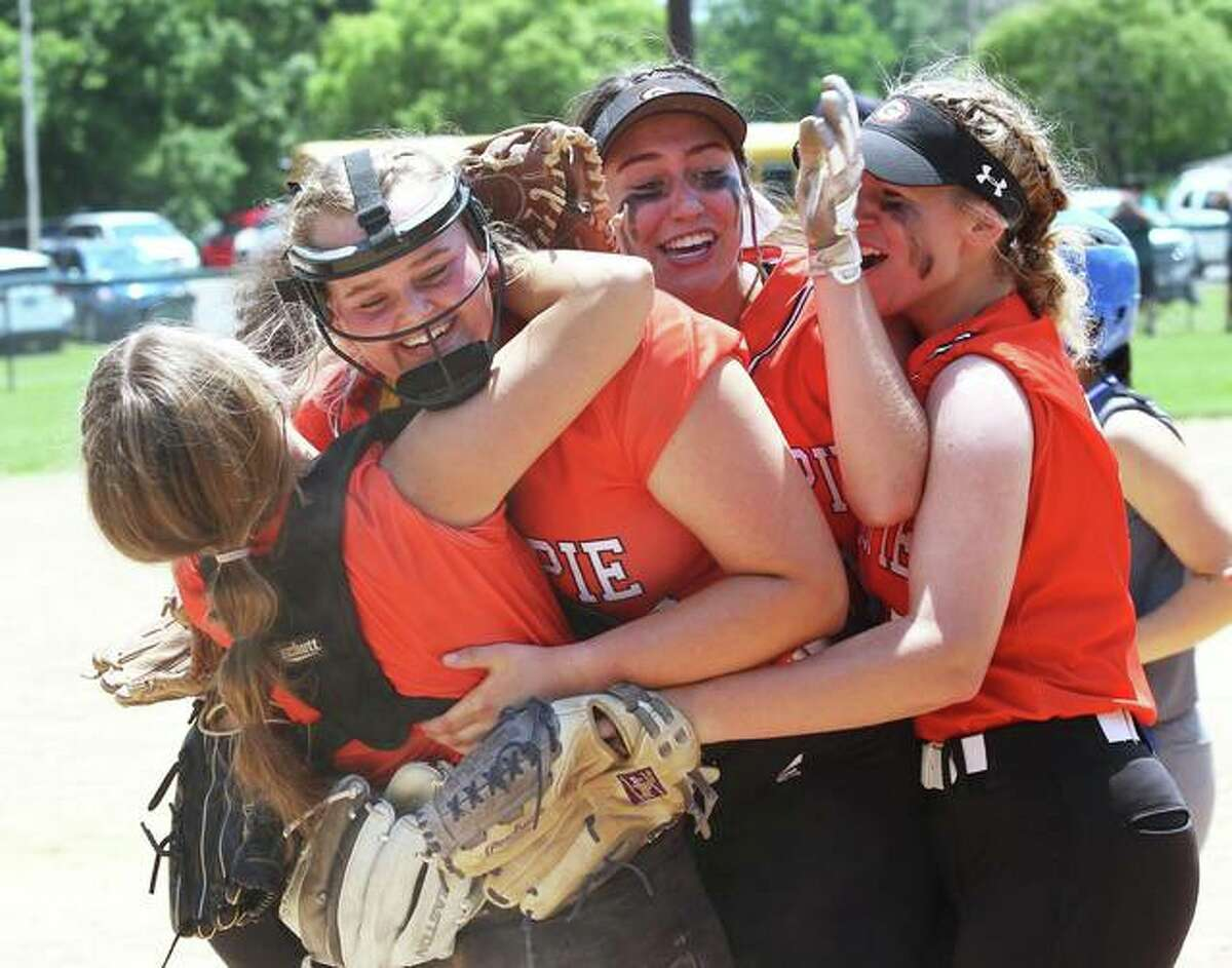 Gillespie catcher Hannah Barrett (left) puts a winning hug on pitcher Sydney Bires as Keaton Link (second left) and Megan Rife (right) join in after the final out of the Miners' 2-0 win over Marquette Catholic in a Class 2A regional title game Saturday at Moore Park in Alton.