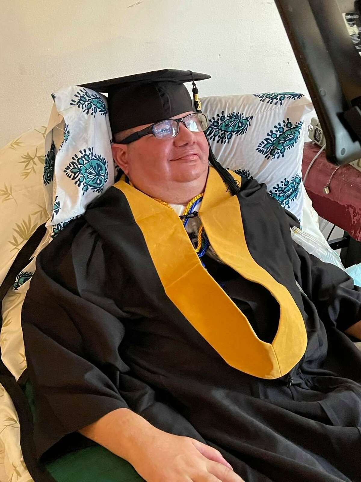 Eliseo Ilarraza wears his cap and gown for his online master's degree graduation ceremony from Our Lady of the Lake University.