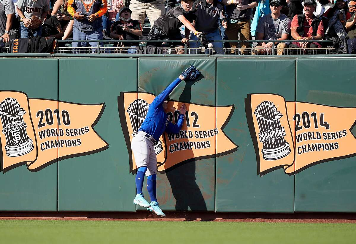 Cubs left fielder Joc Pederson collides with the wall as Alex Dickerson's deep fly goes for a solo homer in the third inning.