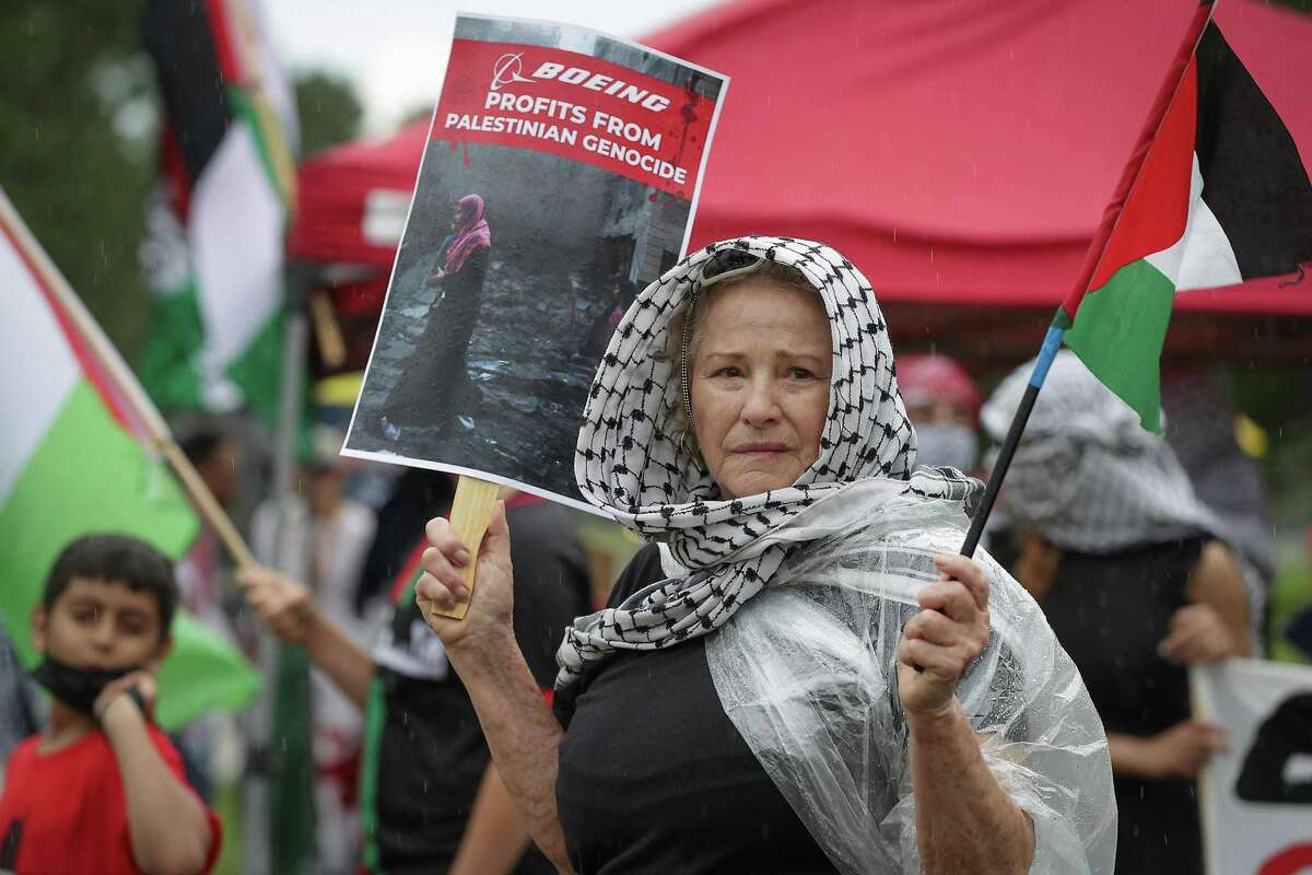 Julianne Gustafson-Lira hold signs in front of the Boeing Company Saturday, June 5, 2021, in Houston. Houstonians gathered at Boeing to commemorate the 54th anniversary of the continued mass expulsion of Palestinians that occurred in 1967 at the hands of Israeli forces, also known as the Naksa (