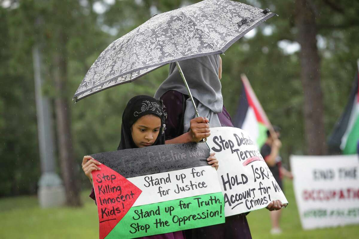 Nylah Omar, 8, holds a sign with her mother Yasmin Husain in front of the Boeing Company Saturday, June 5, 2021, in Houston. Houstonians gathered at Boeing to commemorate the 54th anniversary of the continued mass expulsion of Palestinians that occurred in 1967 at the hands of Israeli forces, also known as the Naksa (