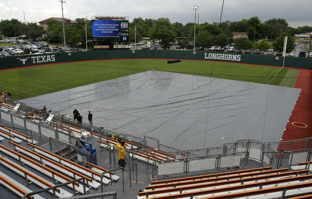 A tarp covers the infield during a lightning delay during the Class 4A UIL state championship game at Red & Charline McCombs Field, Saturday, June 5, 2021, in Austin.