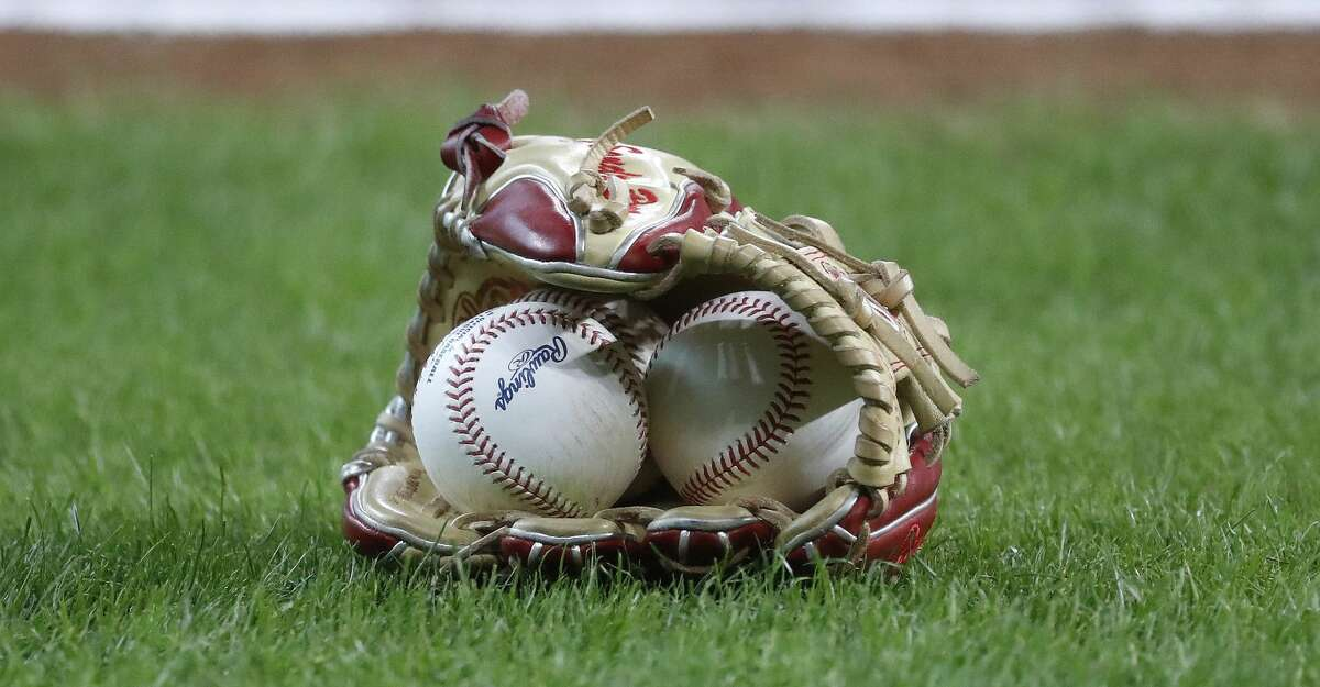 A glove and baseballs on the field before the start of the first inning of an MLB baseball game at Minute Maid Park, Tuesday, June 1, 2021, in Houston.