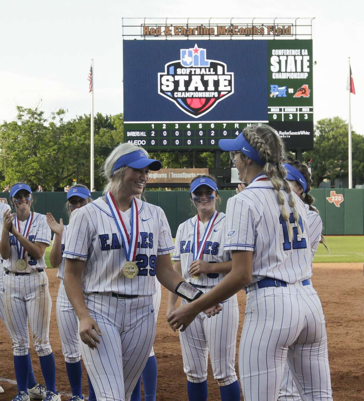 Barbers Hill starting pitcher Sophia Simpson, left, is greeted by Samantha Landry after being named MVP