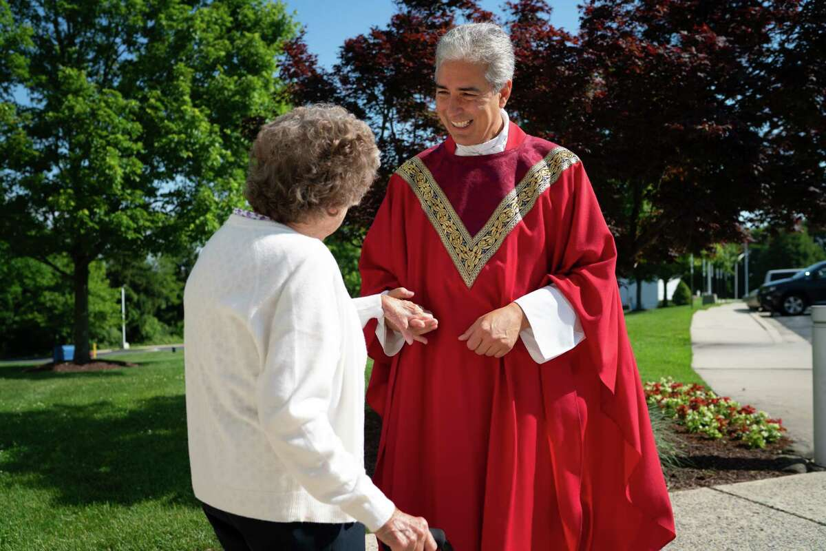 Monsignor Edward Filardi of St. Paul Catholic Church in Damascus, Md., greets his community after a Saturday service on June 5. He is holding the hand of Virginia Rhodes, an original members of the parish who will be turning 100 on July 17.