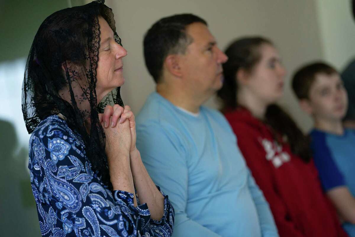 Julie Meyer, of Gaithersburg, Md., prays with her family during a mass at Saint Paul Catholic Church in Damascus, Md., on June 5.