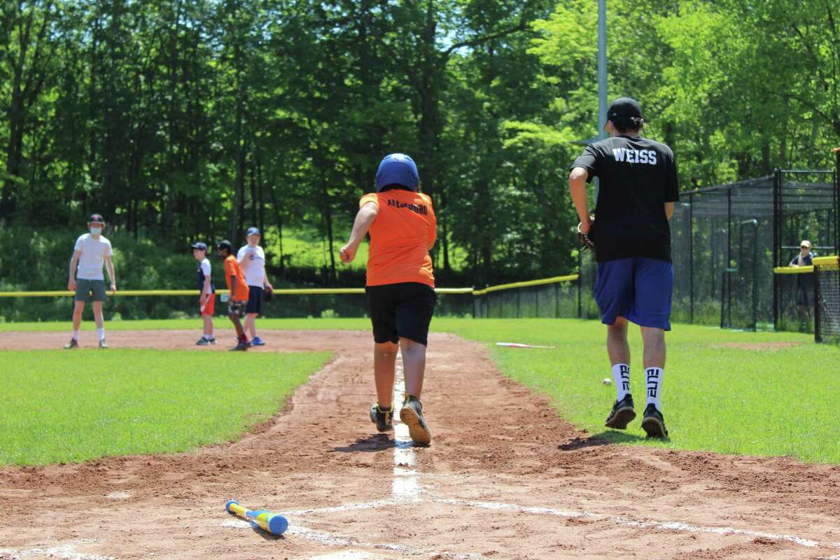 Holland Division player Alejandro darts for first base with his buddy, Danny Weiss, by his side. The seven-person team had its last game of the season on Saturday at Jensen Field in Ridgefield.