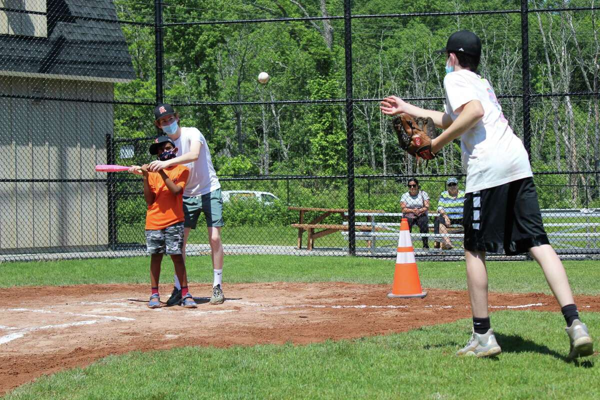 Holland Division player Atharv receives some help at bat from his buddy Milo Rosenzweig as Cormac Bellotti throws a pitch. The seven-person team had its last game of the season on Saturday at Jensen Field in Ridgefield.