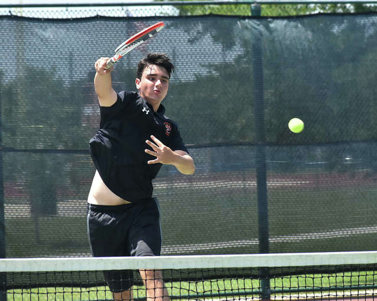 Edwardsville's Michael Karibian slams down a shot during his doubles match in the Class 2A Belleville West Sectional final on Saturday in Belleville.