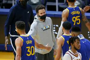 Klay Thompson of the Golden State Warriors greets teammates during a time out in the third quarter against the Cleveland Cavaliers at Chase Center on February 15, 2021.