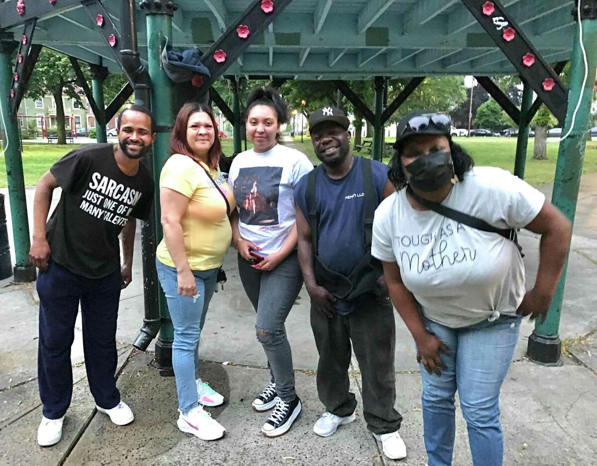 In Washington Park in Bridgeport's East Side neighborhood, skeptics talk about the vaccine. From left, David Brown, who has been vaccinated; Rahseeda Crawford and her daughter, Chaasia Crawford; Marlon Standburry; and Staff Crawford, a cousin of Rahseeda and Chaasia.