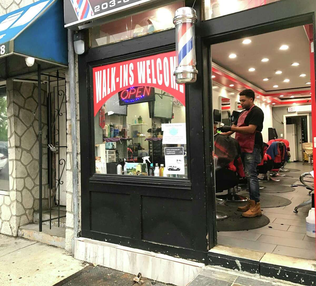 Darlin Santiago, owner of El Tipo barbershop in Bridgeport's East Side, said his customers are hesitant but rlling up their sleeves for the COVID vaccine.