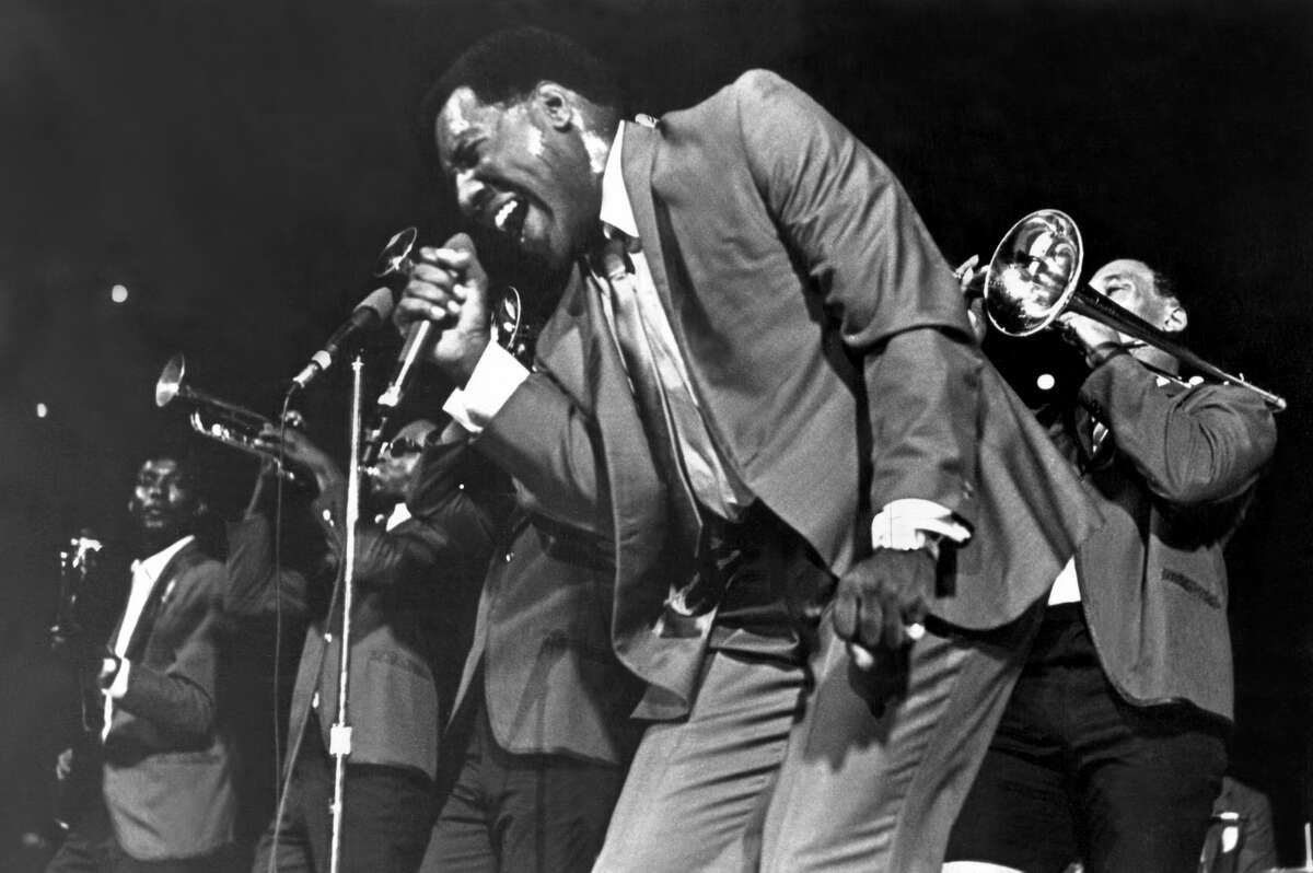 Soul singer Otis Redding passionately sings with his horn section behind him as he performs onstage in 1967.