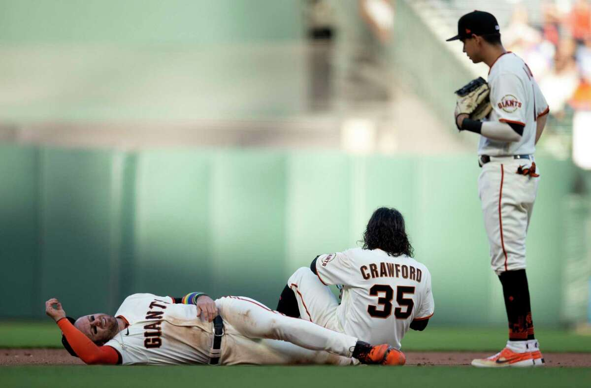 San Francisco Giants third baseman Evan Longoria, left, and shortstop Brandon Crawford (35) lay on the ground after colliding while pursuing a grounder by Chicago Cubs?• Anthony Rizzo during ninth the inning of a baseball game, Saturday, June 5, 2021 in San Francisco, Calif. Second baseman Mauricio Dub-n checks in on his teammates. Longoria left the game, but Crawford played out the inning.