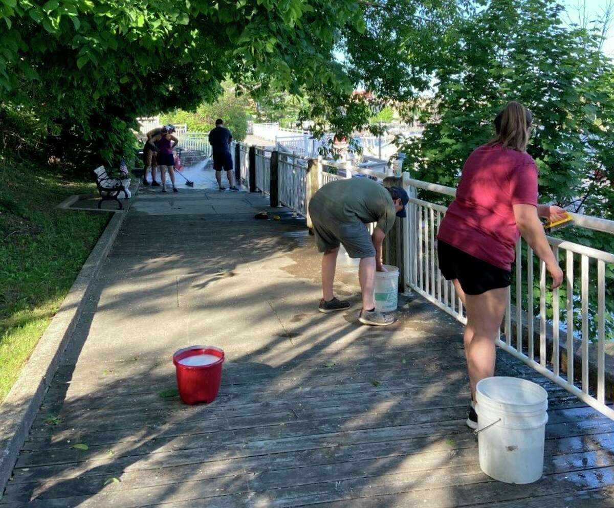 Volunteers from the Spicer Group scrub handrails along the Manistee Riverwalk on Saturday. (Courtesy photo)