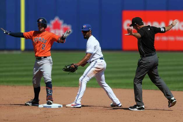 Houston Astros' Alex Bregman, left, calls himself safe next to Toronto Blue Jays second baseman Marcus Semien, center, with second base umpire Pat Hoberg, right, after hitting a double during the eighth inning of a baseball game in Buffalo, N.Y., Sunday, June 6, 2021. (AP Photo/Joshua Bessex) Photo: Joshua Bessex, Associated Press / Copyright 2021 The Associated Press. All rights reserved