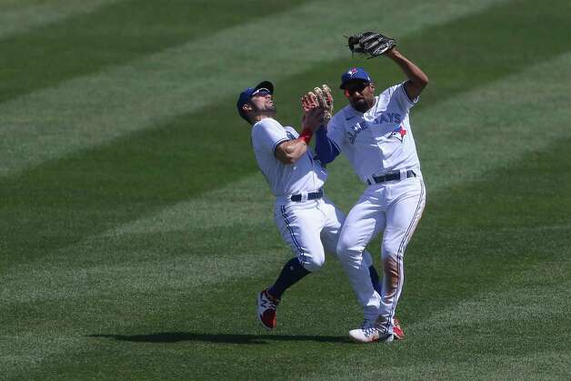 Toronto Blue Jays second baseman Marcus Semien, right, collides with center fielder Randal Grichuk, left, while making a catch during the seventh inning of a baseball game against the Houston Astros in Buffalo, N.Y., Sunday, June 6, 2021. (AP Photo/Joshua Bessex) Photo: Joshua Bessex, Associated Press / Copyright 2021 The Associated Press. All rights reserved