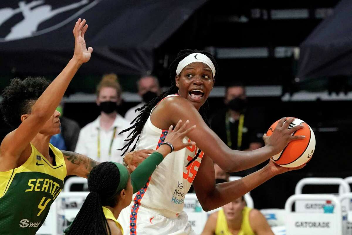 Connecticut Sun's Jonquel Jones, right, looks for room to pass against the Seattle Storm during the first half of a WNBA basketball game Tuesday, May 25, 2021, in Everett, Wash. (AP Photo/Elaine Thompson)