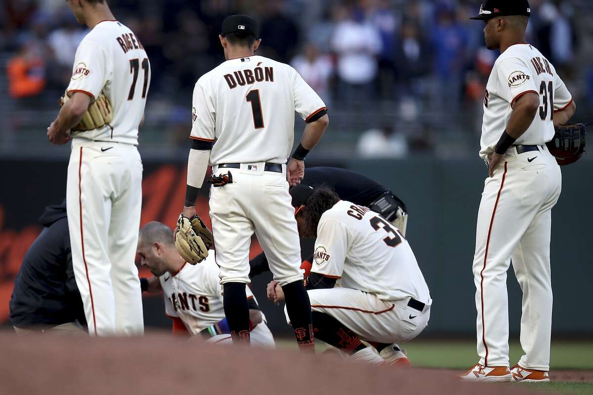 San Francisco Giants third baseman Evan Longoria (10) sits up after colliding with shortstop Brandon Crawford during the ninth inning of the team's baseball game against the Chicago Cubs on Saturday, June 5, 2021, in San Francisco. (AP Photo/Scot Tucker)
