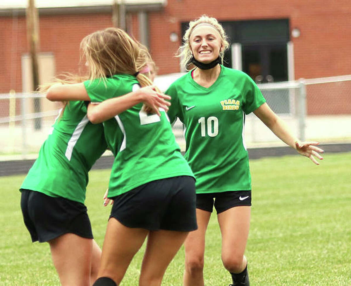 Southwestern's Morgan Durham (10) runs in to join celebrating teammates Mac Day and Ali Wilson (left) after Wilson scored a goal against Carlinville in a Class 2A postseason match Tuesday in Piasa.