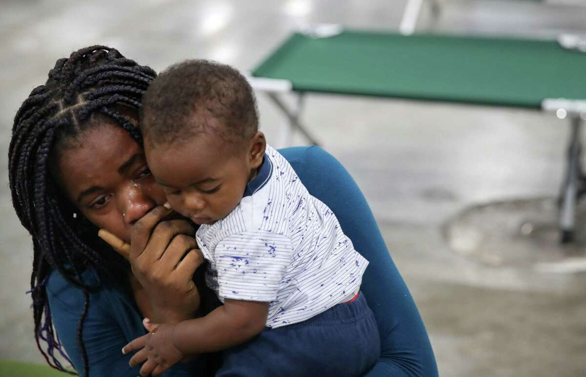 Jouseline Metayer, a Haitian migrant, cries as she holds her son Jayden Metayer and talks about how she was separated from her partner after crossing the southern border, during an interview Saturday, June 5, 2021, at a shelter in Houston. She said she doesn't know where she should go, because her partner had the phone number. She also said her child has trouble sleeping, and that her partner would help put her child to sleep. She said she doesn't know what to do without him.