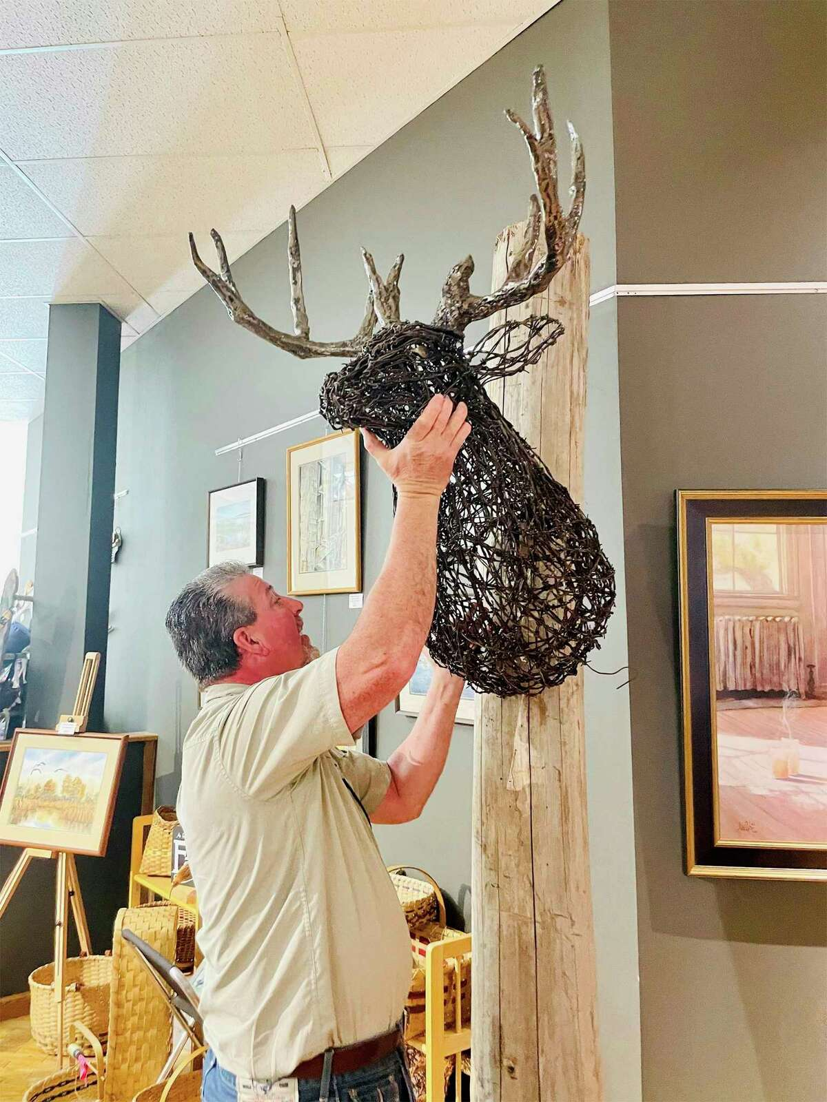 Barbed wire sculptor Jeff Best hangs his deer head sculpture on a post at Artworks. Wild Things: An Exhibit of All Things Animalruns through July 1. (Courtesy/Artworks)