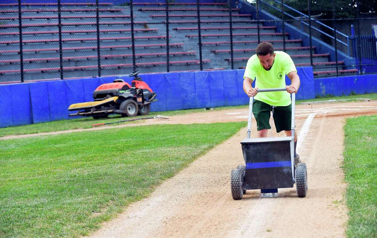 Mike Pinto, an employee with the City of Stamford Parks and Recreation Department layouts and stripes the batters box at Cubeta Stadium in preparation for games on July 28, 2020 in the Stamford Babe Ruth Baseball League in Stamford, Connecticut. Pinto was be helped by fellow employee Gamalier Feliciano as the two endured sweltering heat while maintaining one of a couple of dozen city fields around Stamford.