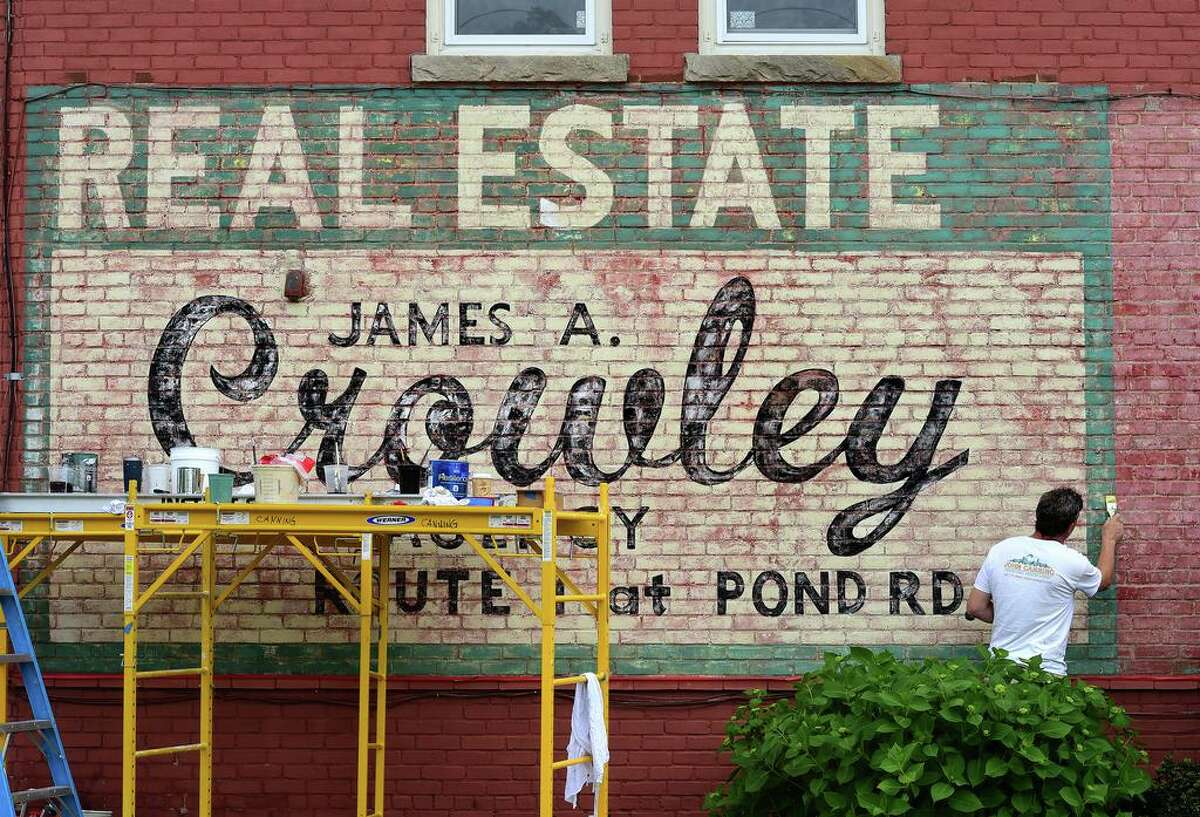 Robert Schwarz of the John Canning Company restores an old advertisement for the James A. Crowley Agency on a building at the corner of Sheffield and Main Street in Old Saybrook.