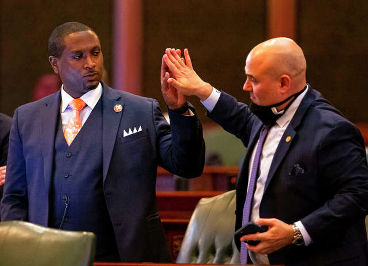 State Rep. Maurice West, D-Rockford (left) gets a high-five from fellow state Rep. Jonathan Carroll, D-Northbrook, after passage of Senate Bill 825, an election omnibus bill which would change Illinois' 2022 primary election from March 15 to June 28 along with making voter access changes.