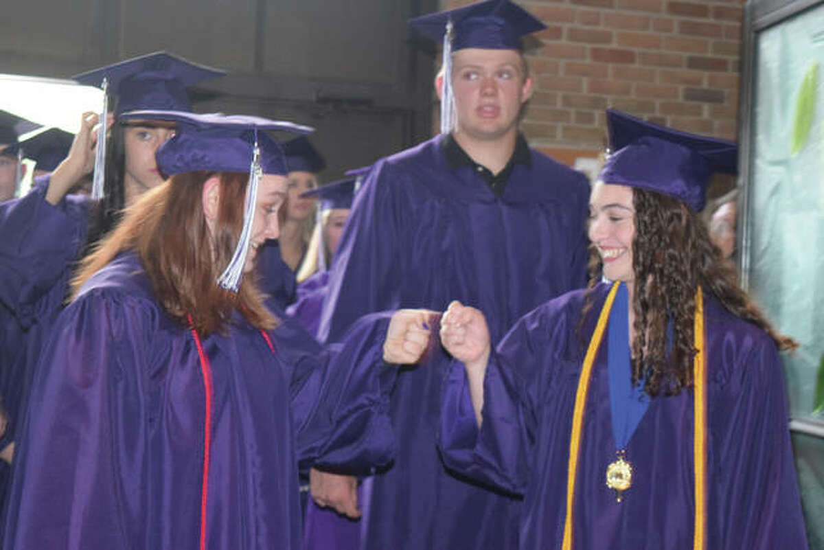 Routt Catholic High School students celebrate graduation by tossing caps into the air Sunday.