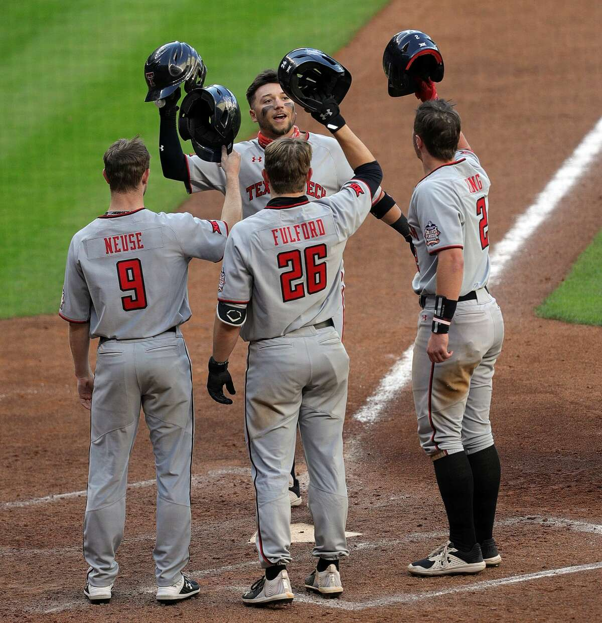 HOUSTON, TEXAS - MARCH 06: Cal Conley #13 of the Texas Tech Red Raiders is congratulated by Dylan Neuse #9, Braxton Fulford #26 and Jace Jung #2 after hitting a home run in the seventh inning against the Sam Houston State Bearkats at Minute Maid Park on March 06, 2021 in Houston, Texas. (Photo by Bob Levey/Getty Images)
