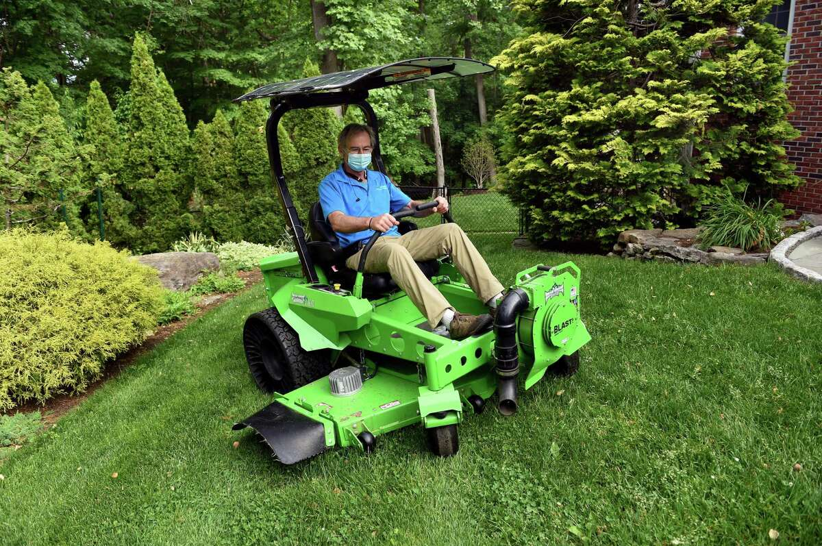 Dan Delvanthal, owner of Mow Green Organic Lawn Care, demonstrates a new battery powered solar charging commercial mower on his lawn in Fairfield on May 28, 2021.