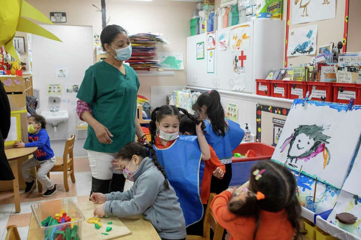 FILE -- A teacher aid works with a class at the Cypress Hills Child Care Corporation in Brooklyn, March 10, 2021. President Biden's plan would increase the scope of the child care industry. (Kirsten Luce/The New York Times)