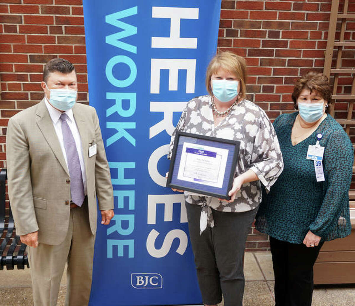 Amy Schuler, center, receives the Leadership Award from AMH President Dave Braasch and Debbie Turpin, chief nursing officer.
