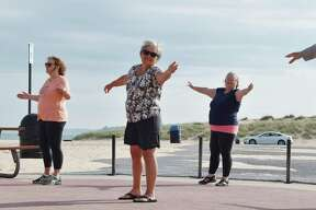 Agroup of nine people could be seen practicingtai chi at Fifth Avenue Beach on Monday morning. (Arielle Breen/News Advocate)