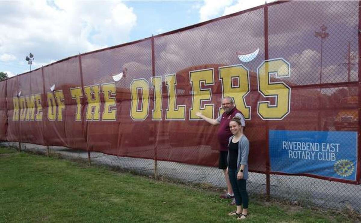 East Alton-Wood River High School Superintendent John Pearson shows the newly installed Oiler fence banner at Memorial Stadium to Riverbend East Rotary Club President-Elect Lindsey Herron. The Rotary Club and an anonymous donor partnered to purchase the banner and a media backdrop banner for the high school.