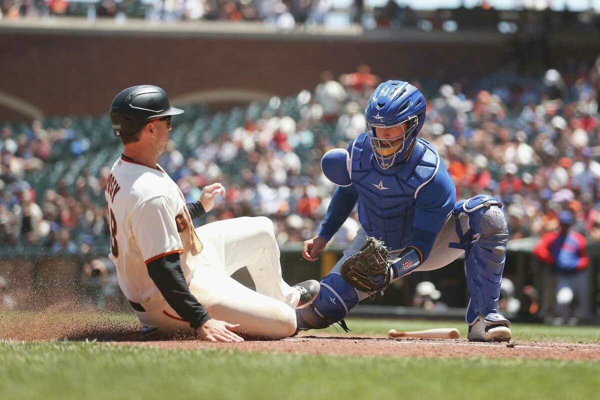 SAN FRANCISCO, CALIFORNIA - JUNE 06: Catcher P.J. Higgins #20 of the Chicago Cubs tags out Buster Posey #28 of the San Francisco Giants at home plate in the bottom of the second inning at Oracle Park on June 06, 2021 in San Francisco, California. (Photo by Lachlan Cunningham/Getty Images)