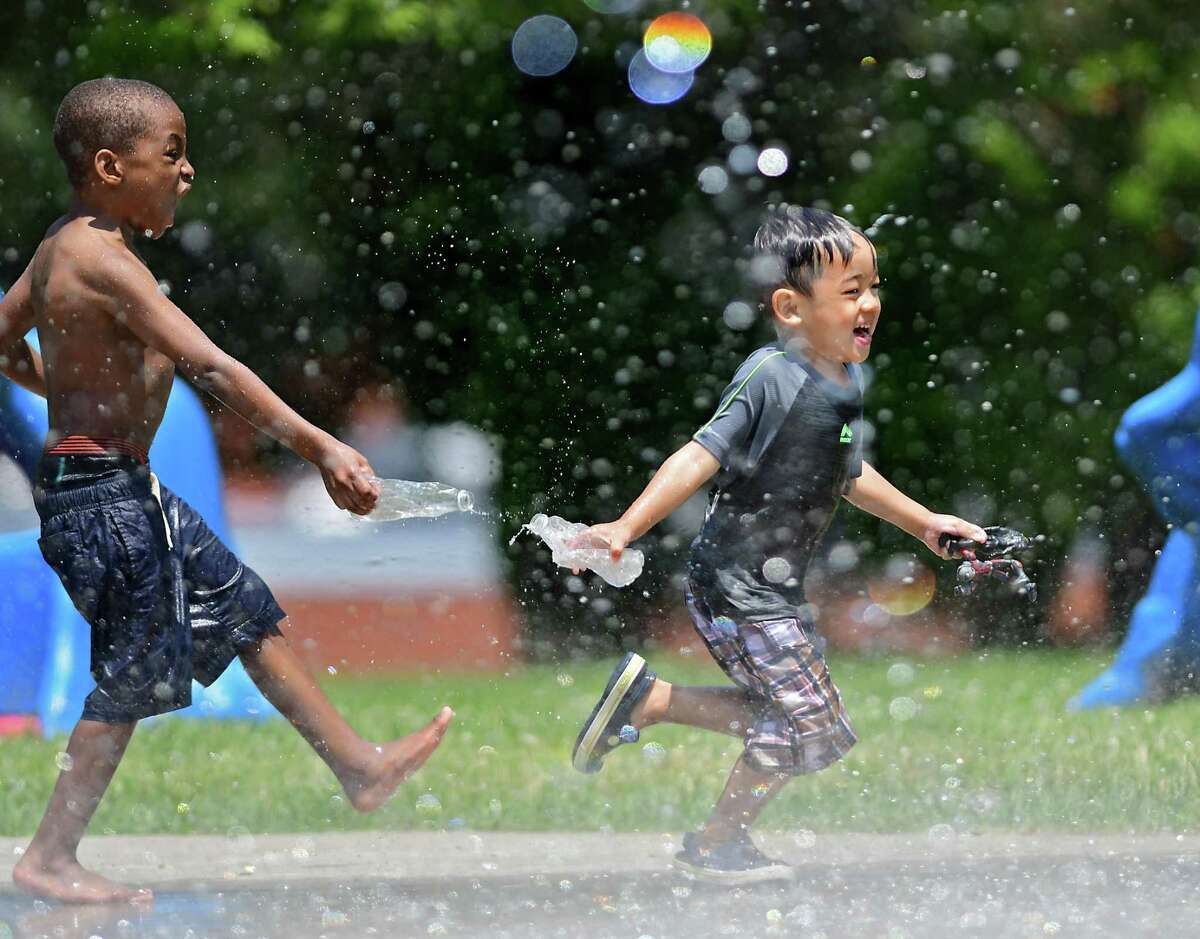 Quincy Washington, 5, of Troy throws water on Tonpaisue Mupwe, 4, of Albany, as they play and keep cool at the splash pad in Lincoln Park on Monday, June 7, 2021 in Albany, N.Y. A heat advisory was issued for another day where temperatures are expected in the 90's. (Lori Van Buren/Times Union)